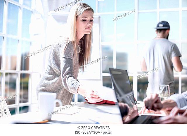 Female designers handing over paperwork in design studio