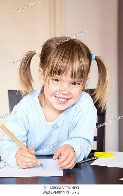 Portrait of smiling little girl with green crayon