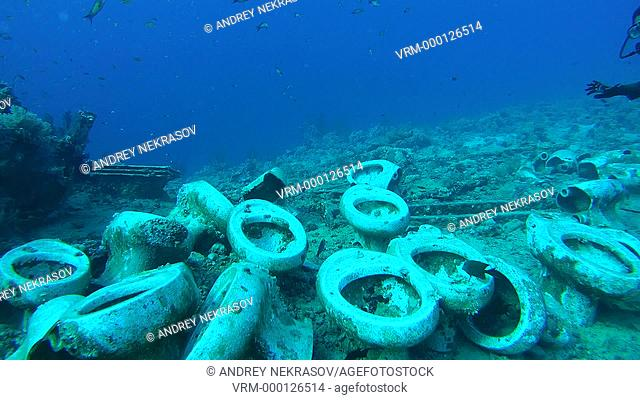 Diver looking at plumbing goods scattered on the sea floor after shipwreck, Ras Mohammad National Park, Red Sea, Egypt