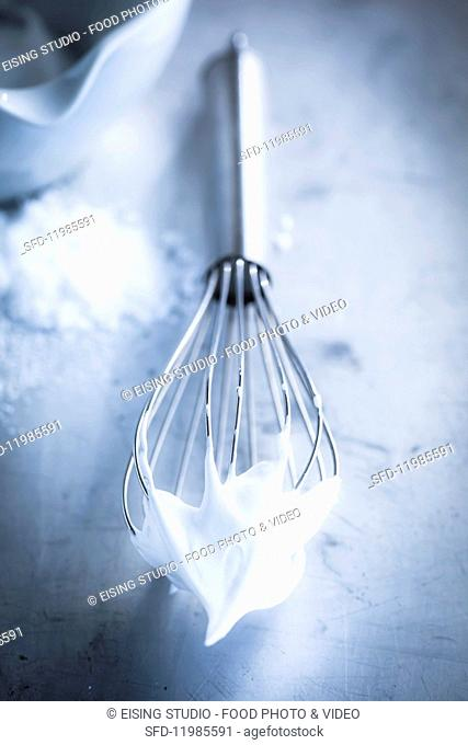 A whisk with whipped egg whites