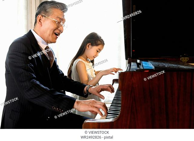 Grandfather and granddaughter play the piano together