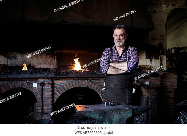 Portrait of confident blacksmith in his workshop