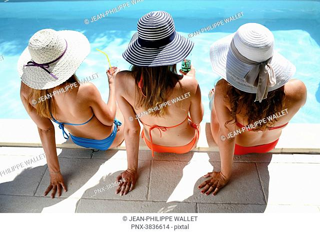 Three beautiful young woman with swimsuit and sun hat sitting by the poolside of resort swimming pool during summer holiday