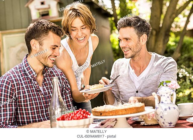 Group of friends enjoying garden party, young woman holding plate with dessert