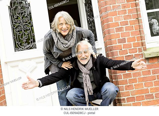 Senior couple by front door, man crouching with open arms