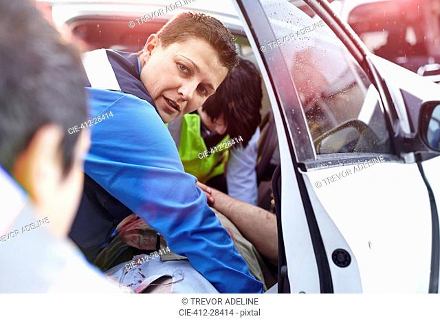 Rescue workers pulling car accident victim from car