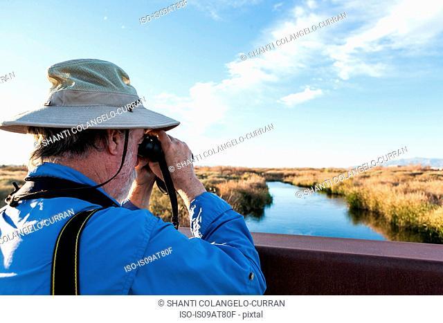 Bird-watcher using binoculars, Las Vegas, Nevada, USA