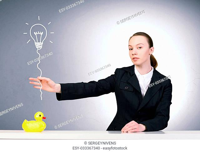 Young businesswoman and yellow rubber duck toy on table