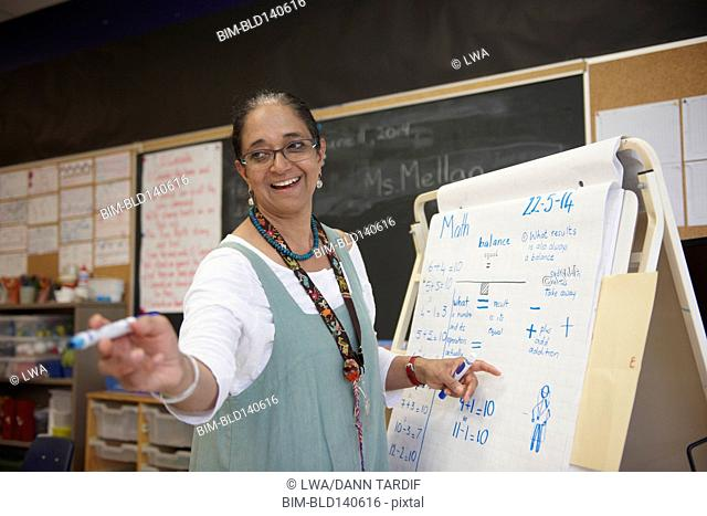 Indian teacher writing on flip chart in classroom