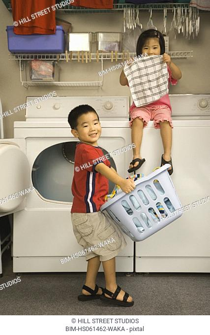 Young Asian brother and sister with clean laundry in laundry room