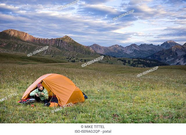 Woman camping, Hasley Basin, West Elk Mountains, Colorado, USA