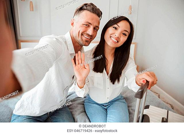 Lovely young couple taking selfie with mobile phone while sitting together on bed at a hotel room with a suitcase