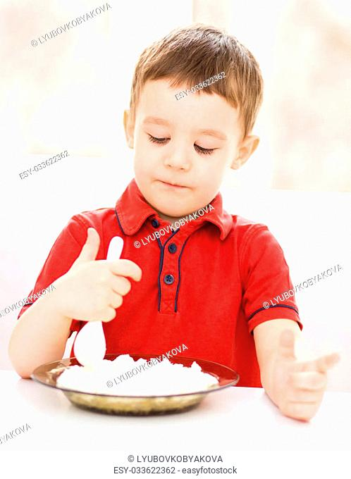 Cute little boy is eating cottage cheese using spoon