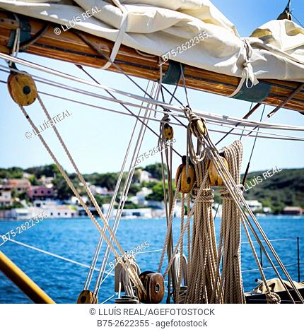 Close up of masts and rigging from a vintage boat, with a blue sky in the background. pulleys, sails and ropes. Port Mahon, Menorca, Biosphera Reserve
