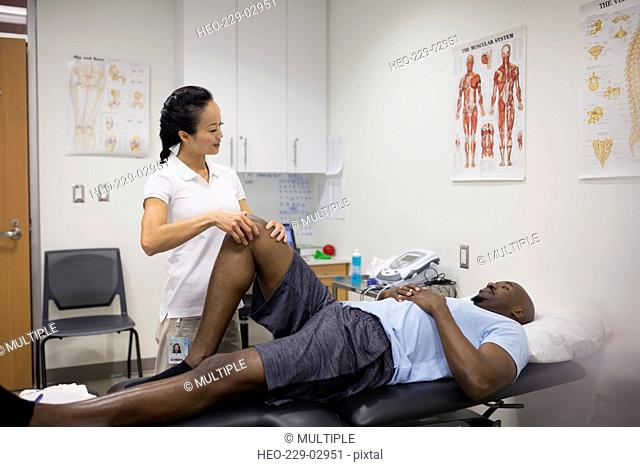 Physical therapist massaging patient knee in examination room