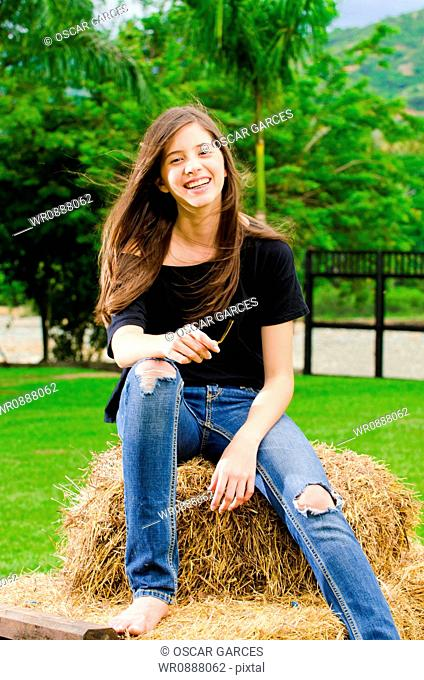 Young Woman Sitting in the Hay