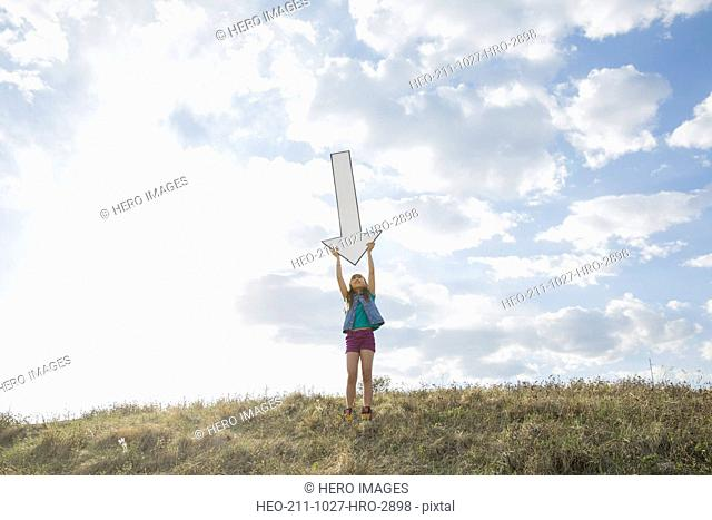 Schoolgirl with arms raised holding downward arrow on field