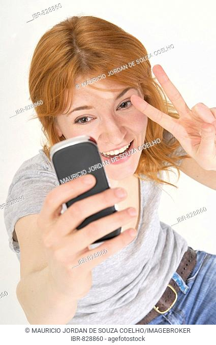 Red-haired, attractive woman writing a text message on her mobile, making the peace sign