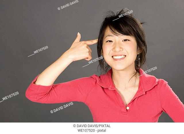 Portrait of a beautiful Asian teenager posing on a gray background with finger pointing at head