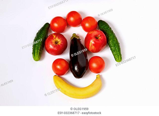 Banana, eggplant, tomatoes, apples and cucumbers are located in the form of a face. There is a light shadow from fruit
