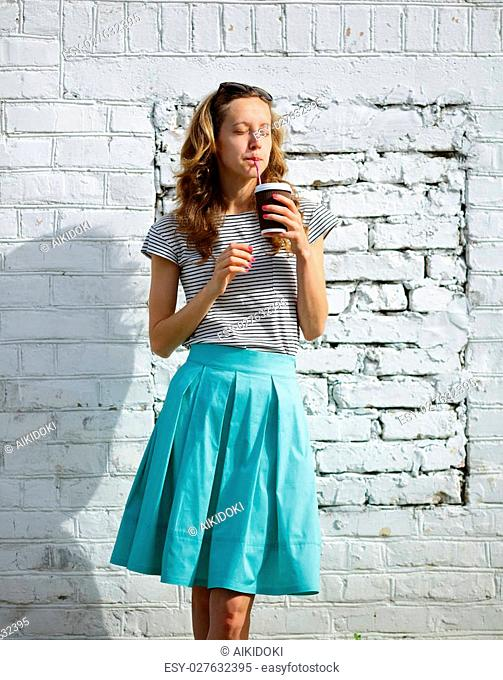 Young woman drinks morning cofee with a disposable cup on the background old brick wall