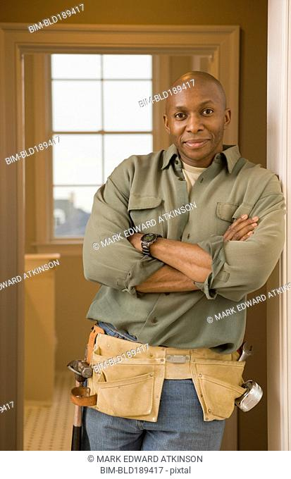 African man wearing tool belt with arms crossed