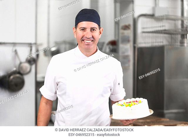 Smiling pastry Chef showing a cake in the pastry shop kitchen