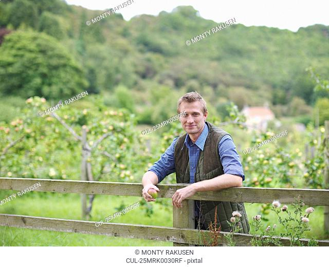 Farmer leans on fence outside orchard