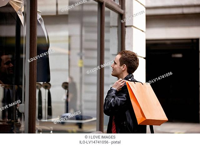 A young man looking in a shop window