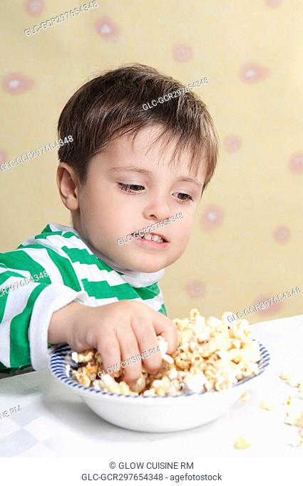 Close-up of a boy playing with popcorns