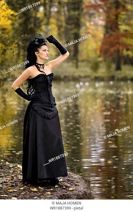 Young woman in Gothic style fashion stands on the waterfront, Croatia, Europe