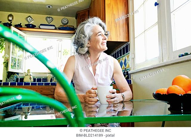 Caucasian woman drinking cup of coffee in kitchen