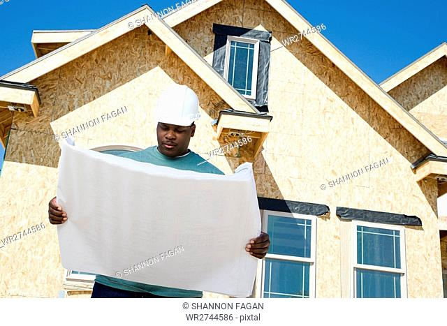 A builder holding a blueprint