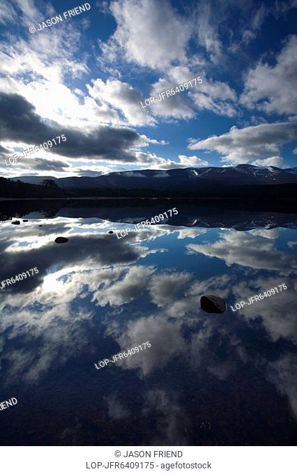 Scotland, Highland, Loch Morlich, Dramatic clouds and Cairngorm mountains reflected upon the still face of Loch Morlich