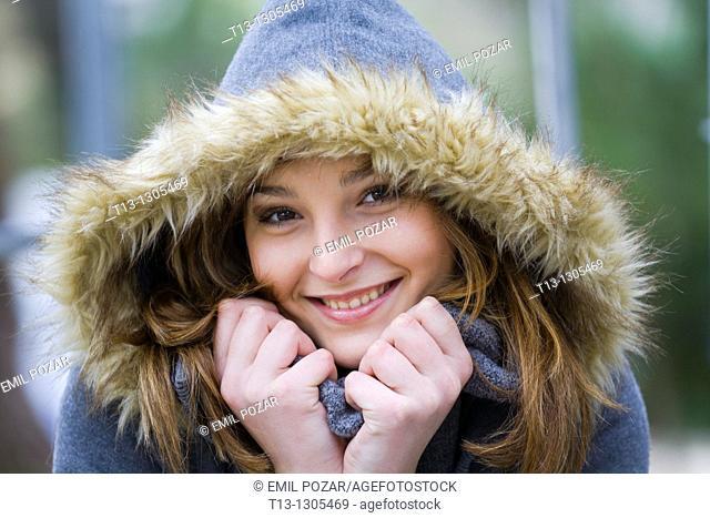 Happy teen girl warm under the hood