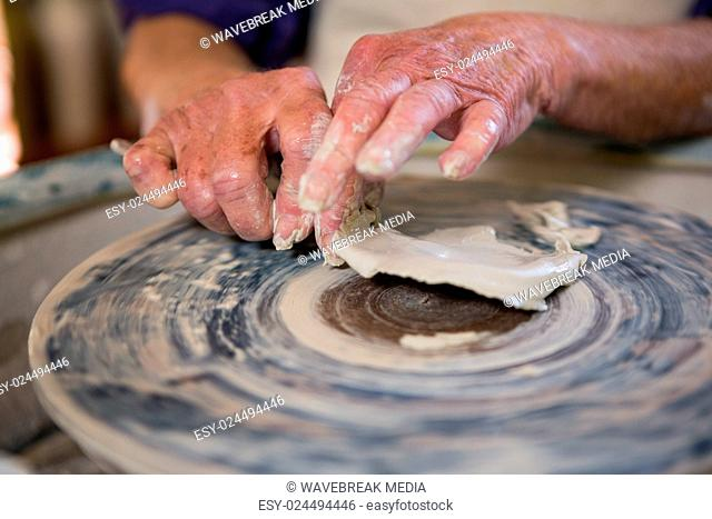 Close-up of potter removing clay from pottery wheel
