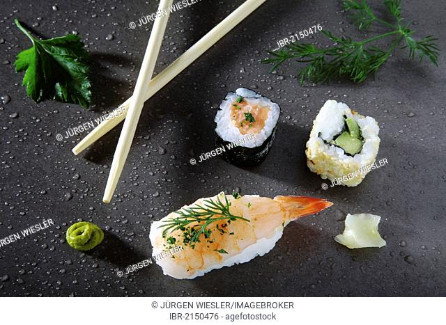 Assorted sushi with ginger and wasabi on a stone surface