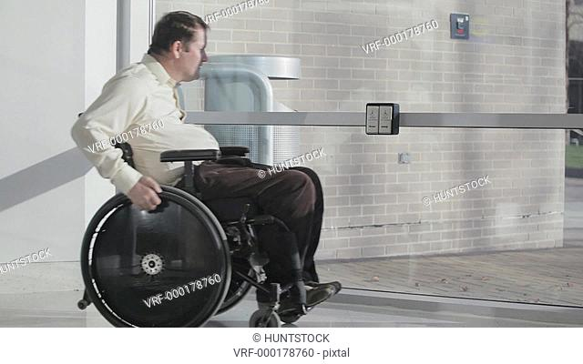 Man with spinal cord injury in wheelchair using automatic door opener to exit building