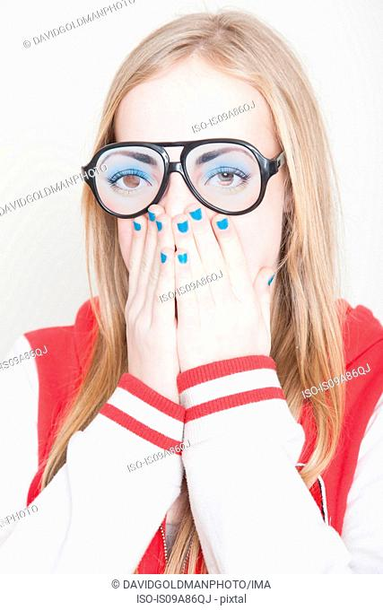 Girl wearing fake spectacles with hands covering her mouth