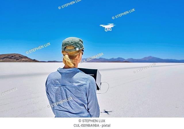Woman on salt flats, flying drone, rear view, Salar de Uyuni, Uyuni, Oruro, Bolivia, South America