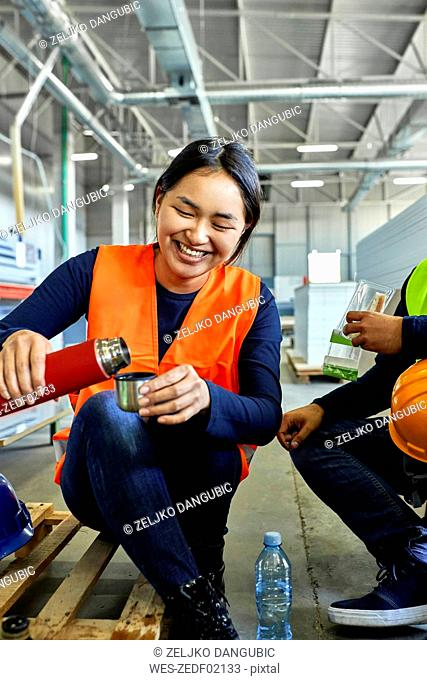 Happy female worker pouring drink into mug during lunch break in factory