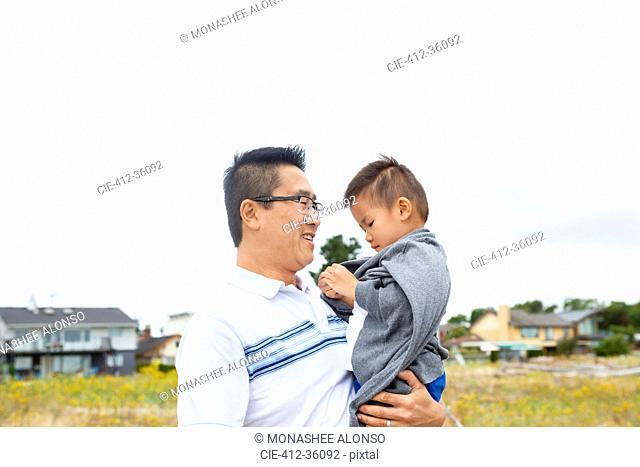 Chinese father holding son in park