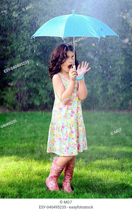 young girl with blue umbrella in the rain