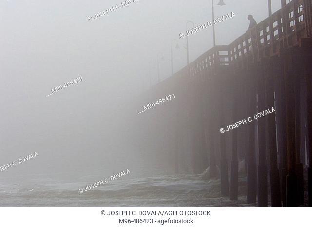 Man on pier in heavy fog. Ventura, California, USA