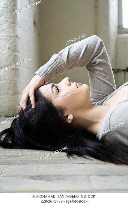 Serious young woman laying on the floor looking up