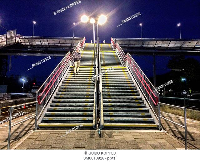 Breda, Netherlands. Stairs to an overhead traverse over the track at central railway station Breda, Netherlands, at night