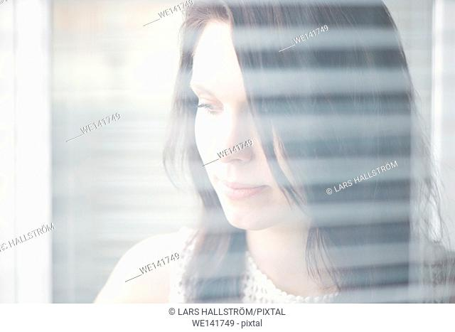 Woman standing by a window. Concept of sadness, waiting and anticipation. Lifestyle image of contemplation