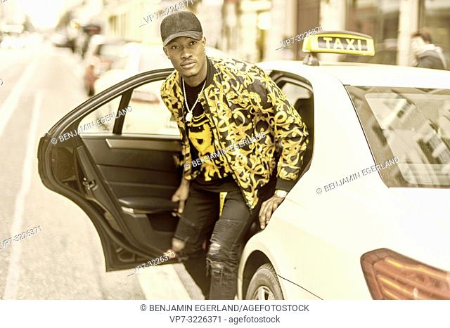 young stylish man getting out of taxi, exiting car, at city street, wearing trendy fashion clothes, in Munich, Germany