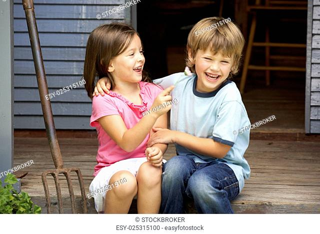 Young brother and sister sitting on veranda
