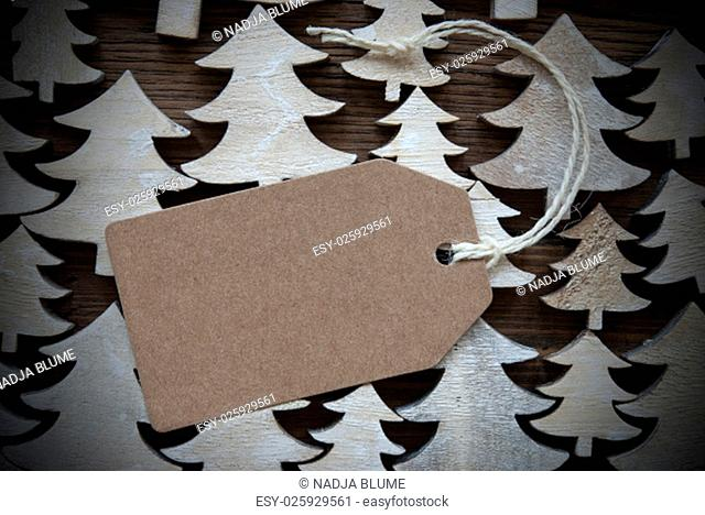 Brown Christmas Label With Ribbon On Wooden Christmas Trees Background. Vintage Style.Label With Copy Space Or Free Text Or Your Text Here For Christmas Or...